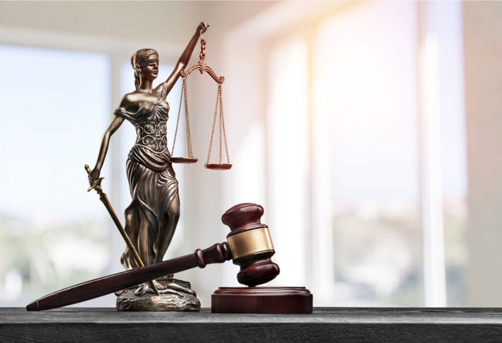 statue of lady justice with scales next to a gavel