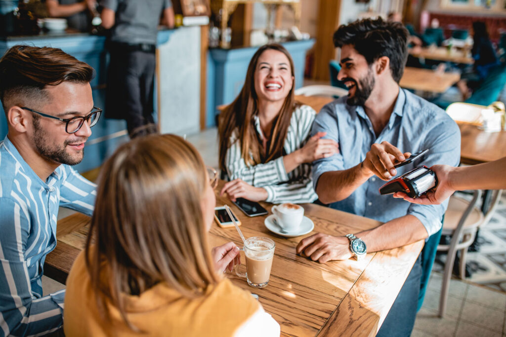 group of friends sitting at a table in a coffee shop using contactless payment with phone