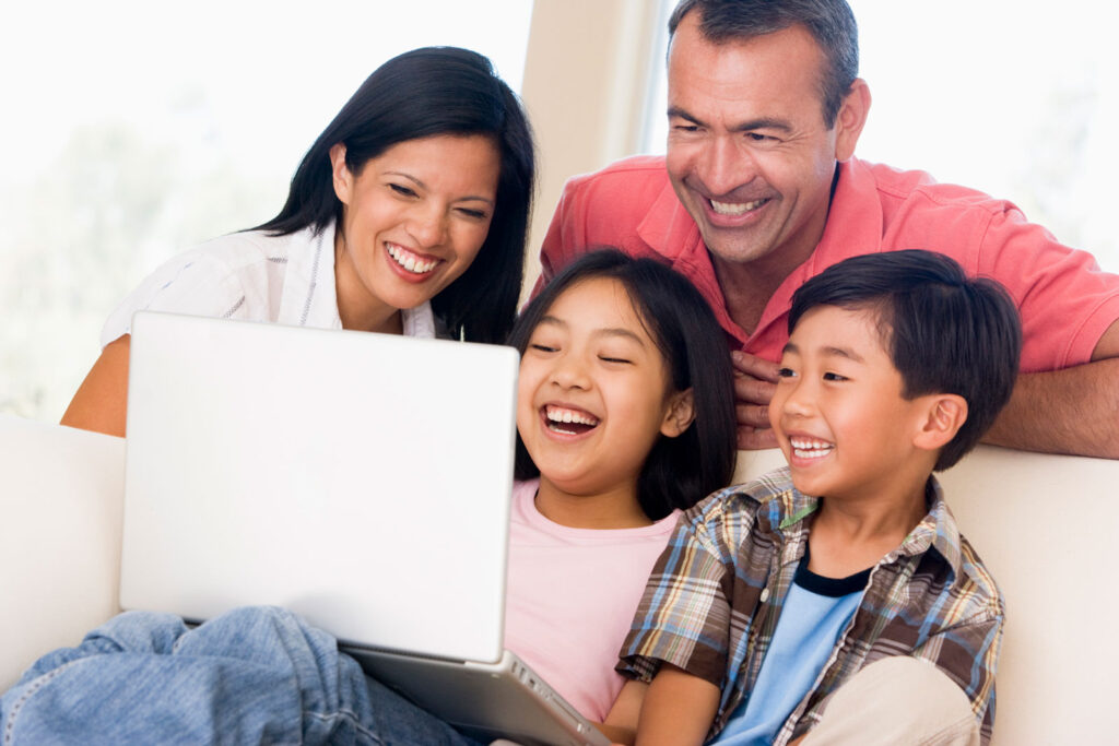 Happy family smiling and looking at the laptop