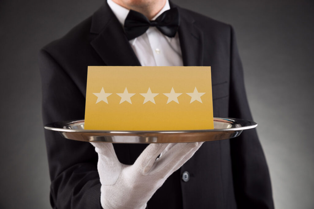 waiter serving gold card with five stars