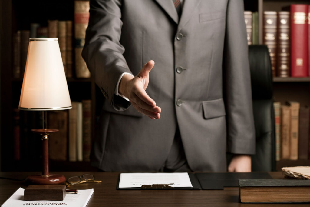 lawyer standing behind desk reaching forward for a handshake
