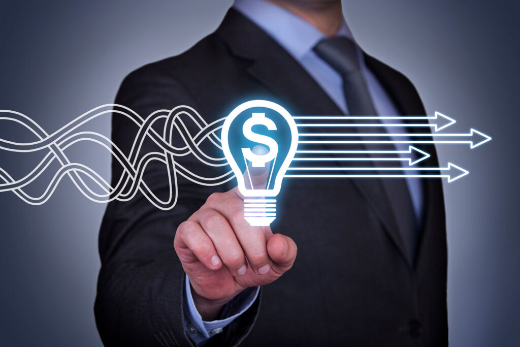 business man pointing at lightbulb with dollar sign towards screen